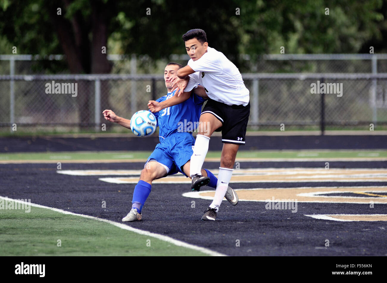 Pair of high school players making solid contact with as they battle for possession of the ball in the box in front - Stock Image