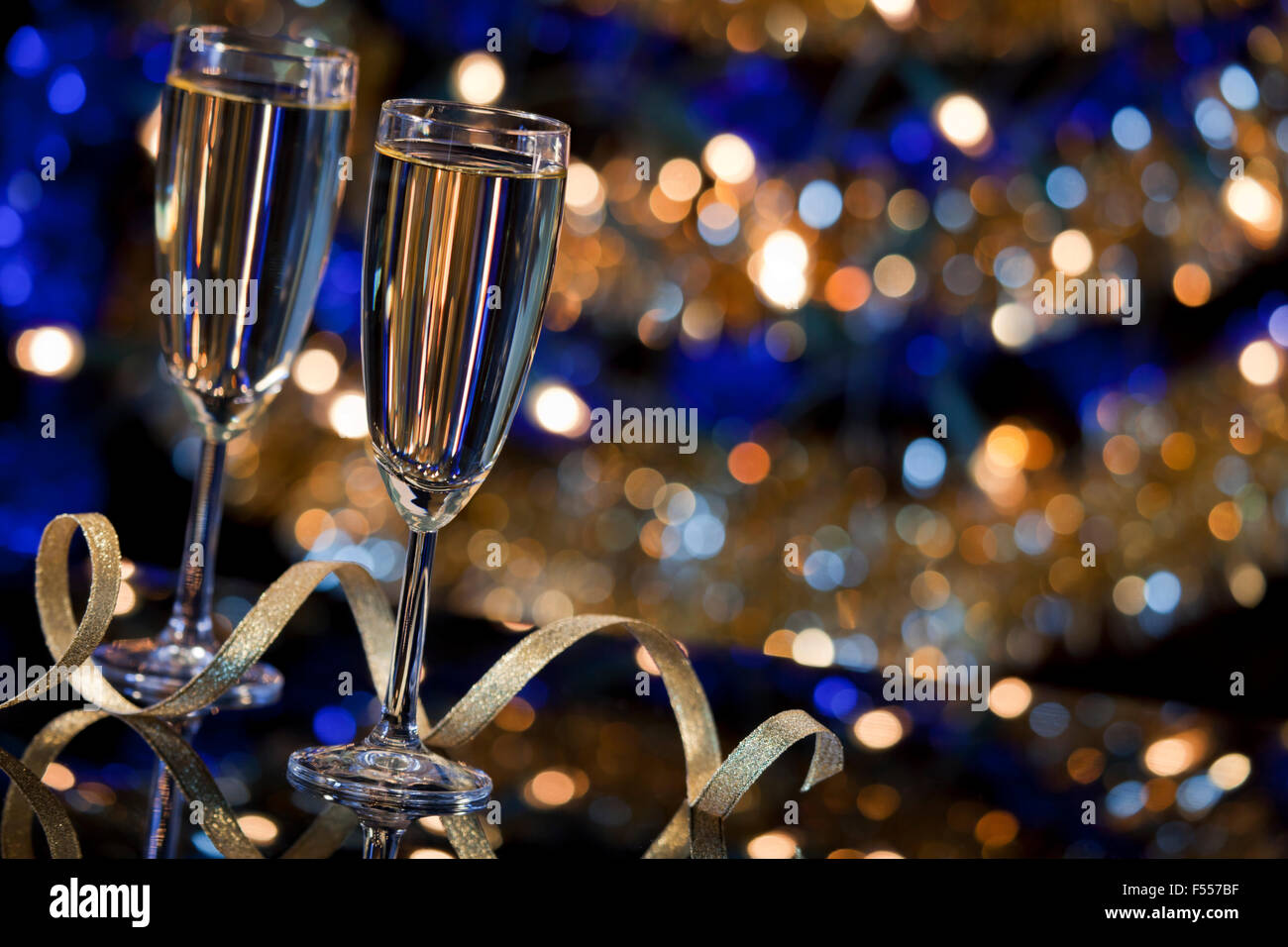 A New Year's Eve scene with champagne glasses and Christmas lights in the background. - Stock Image