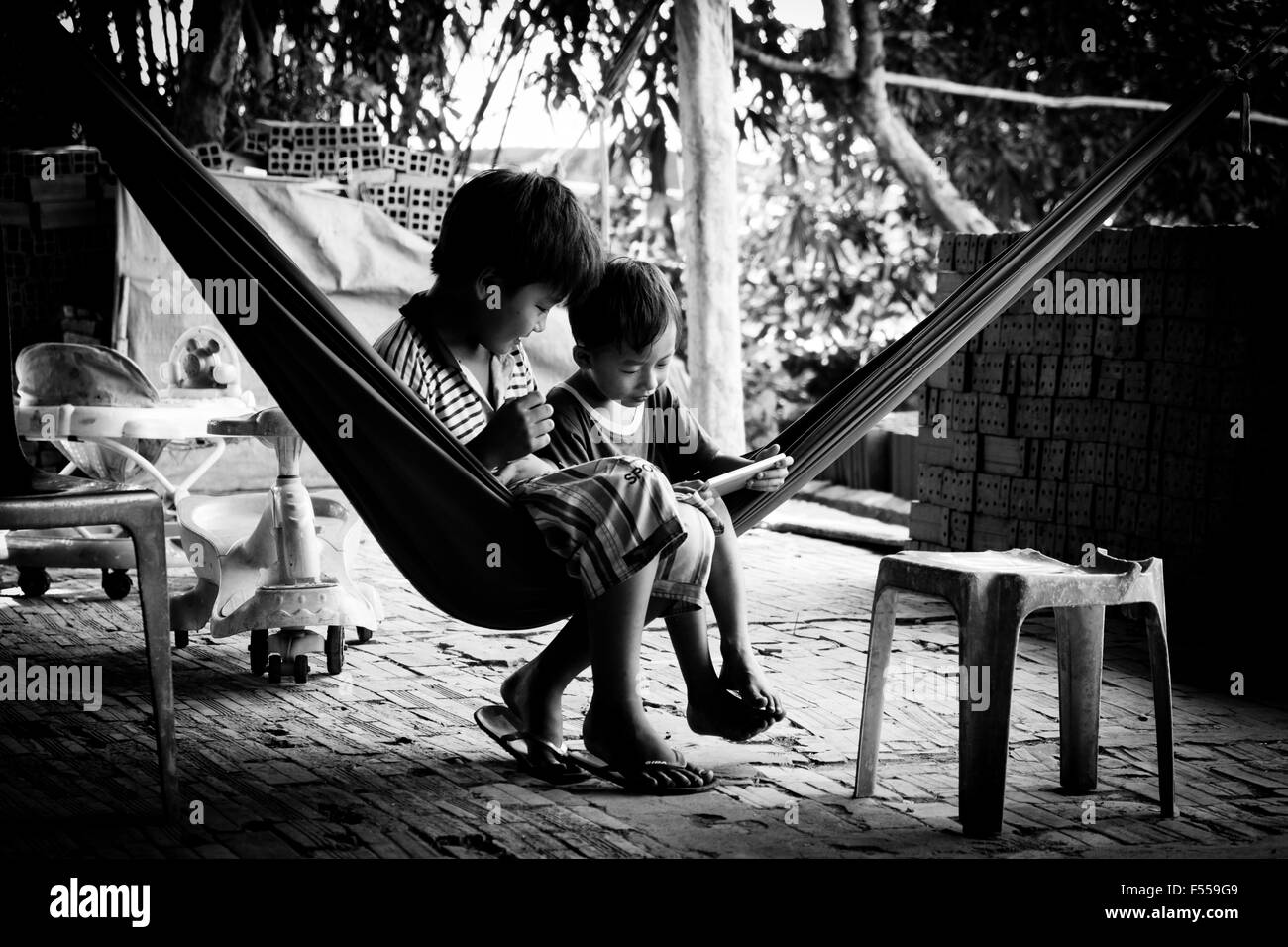 Two boys look at a smart phone while sitting in a hammock in their family-owned brick factory in the Mekong Delta, - Stock Image