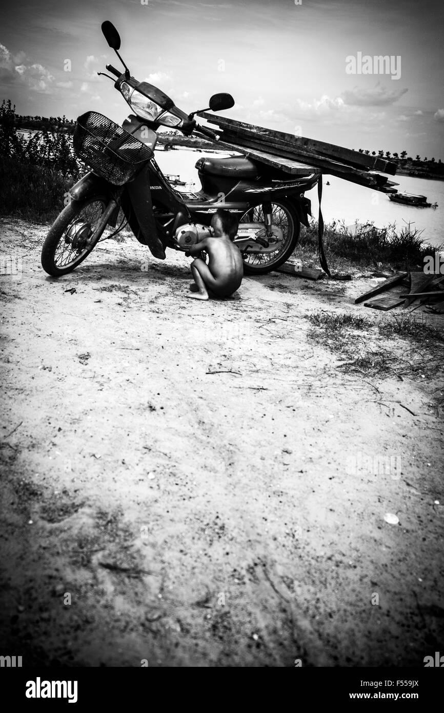 A little boy appears to be fixing a motor bike near Phnom Krom outside of Siem Reap, Cambodia - Stock Image