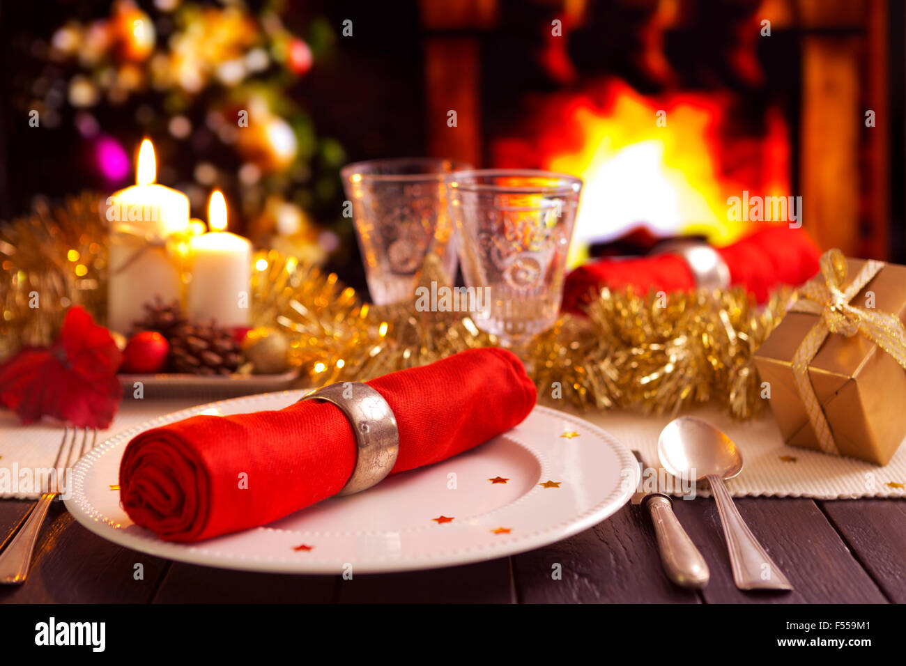 A romantic Christmas dinner table setting with candles and Christmas decorations. A fire is burning in the fireplace and Christm & A romantic Christmas dinner table setting with candles and Christmas ...