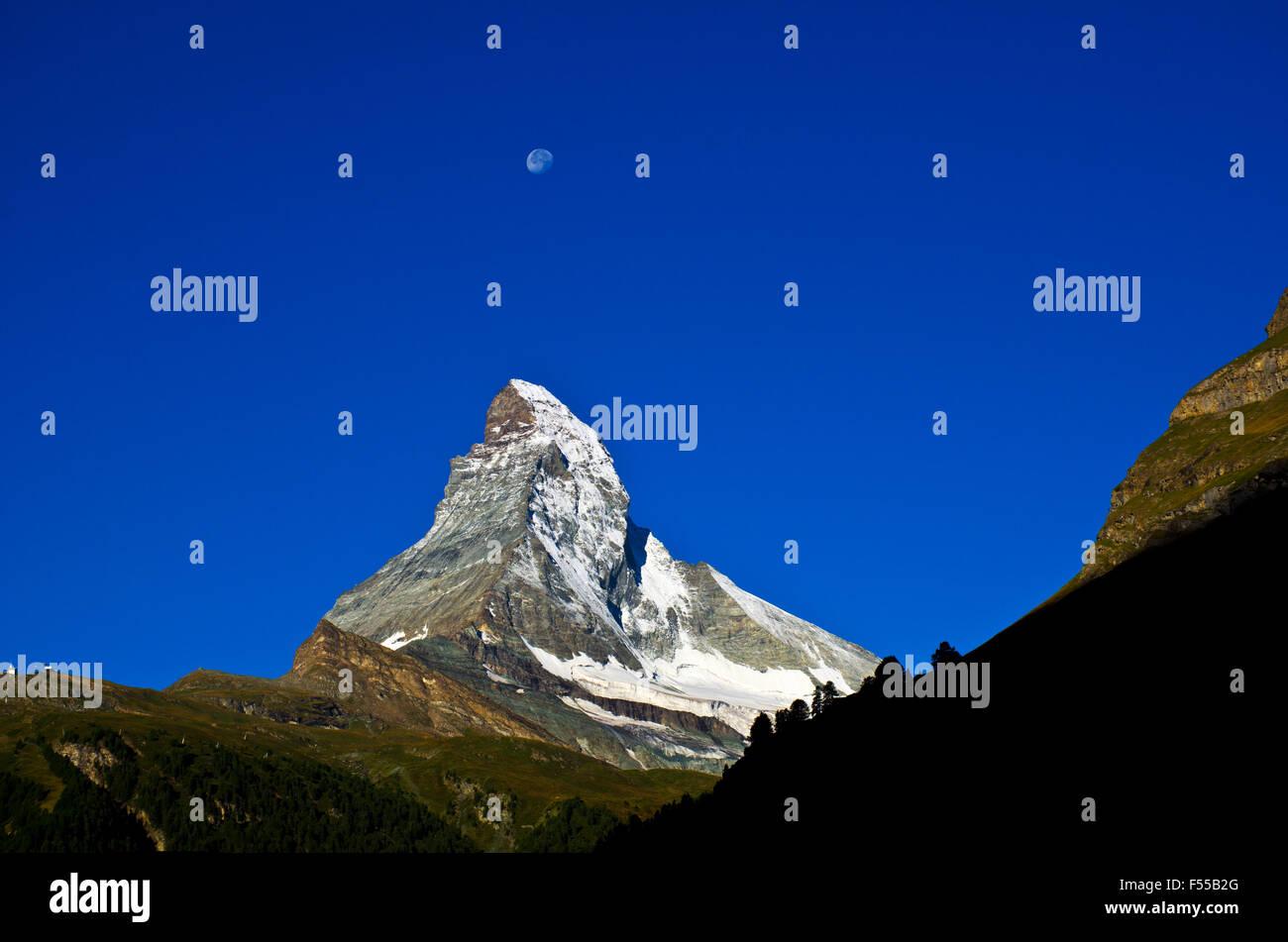 Matterhorn and moon at sunrise seen from Zermatt, Swiss alps, Valais, Wallis, Switzerland - Stock Image