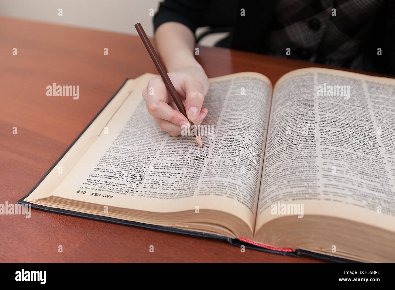 Student holding a pencil in his hand and is studying textbook - Stock Image