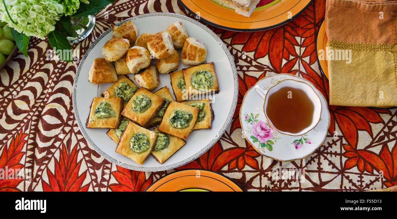 Afternoon tea setting with plate of savory pastries. - Stock Image