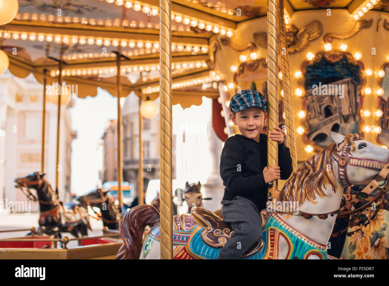 bff941703 Little boy enjoying his ride at carousel in amusement park Stock ...