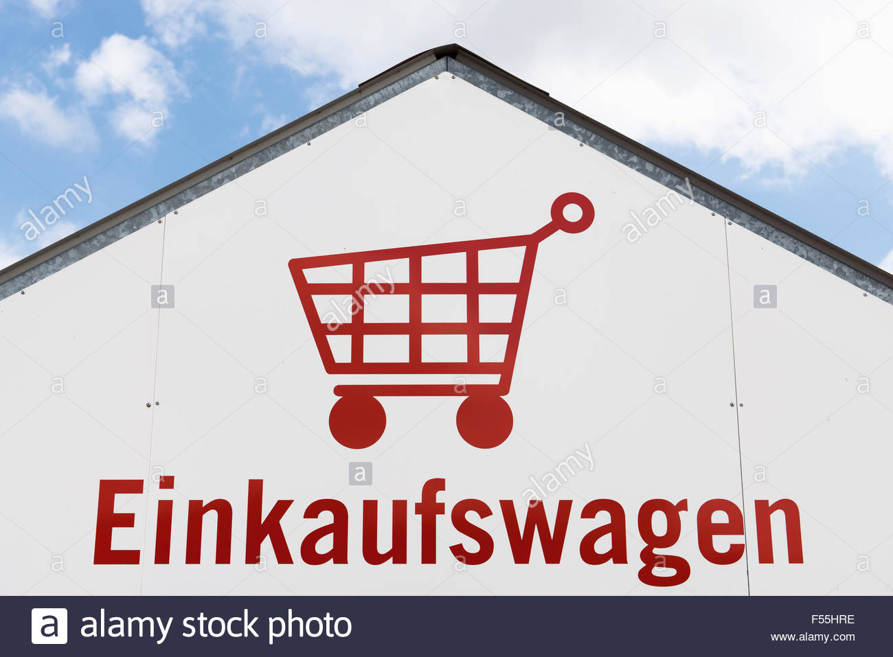 Germany, shopping cart pictogram on a house facade - Stock Image