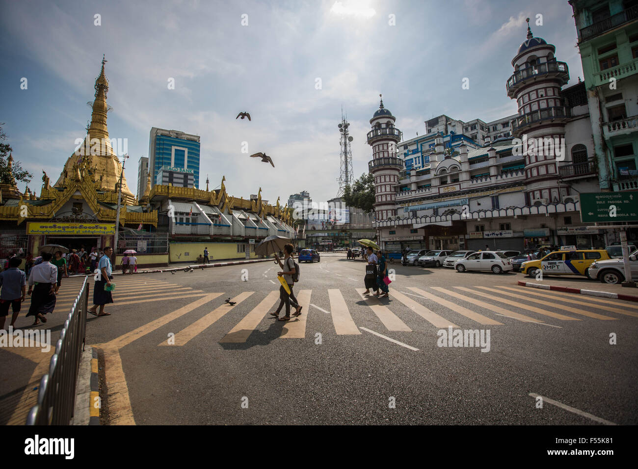 Yangon, Yangon, Myanmar. 28th Oct, 2015. People cross the road between the Buddhist Sule Pagoda and the Muslim Bangali - Stock Image