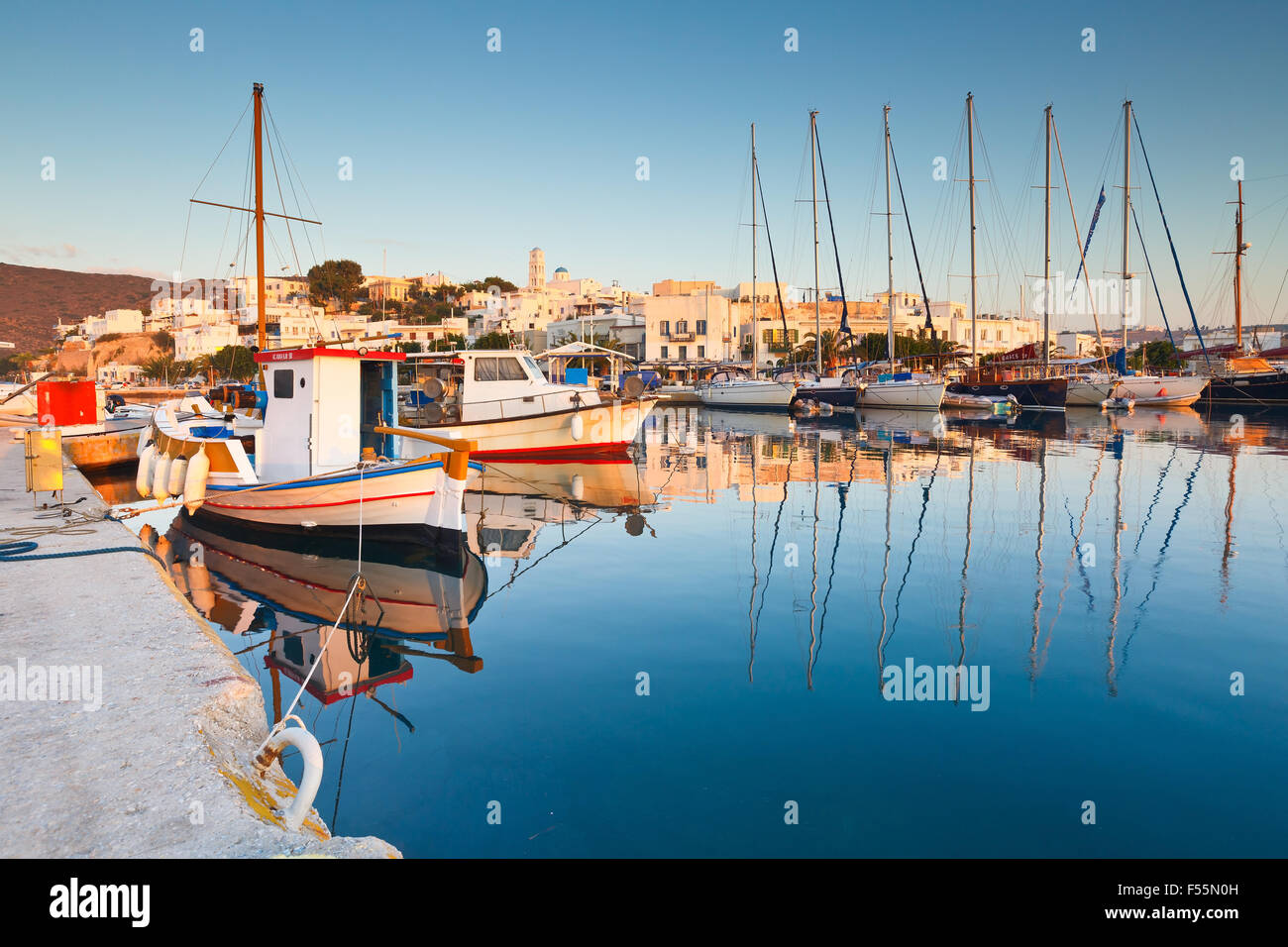 Fishing boats and sail boats in Adamantas harbour on early morning - Stock Image