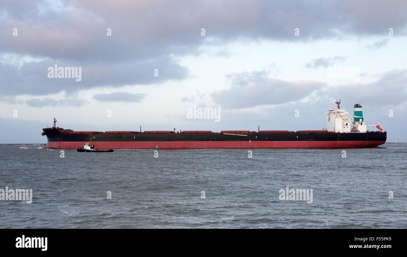 Large ore bulk carrier leaving the Port of Rotterdam. - Stock Image