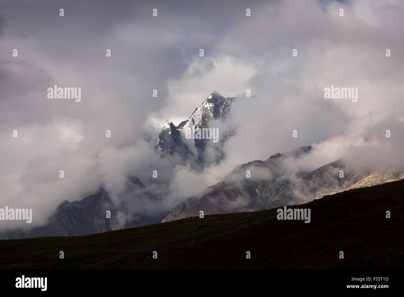 India, Himachal Pradesh, Spiti, Chandra Taal, Snow capped Bhaga Mountains glimpsed through early morning cloud - Stock Image