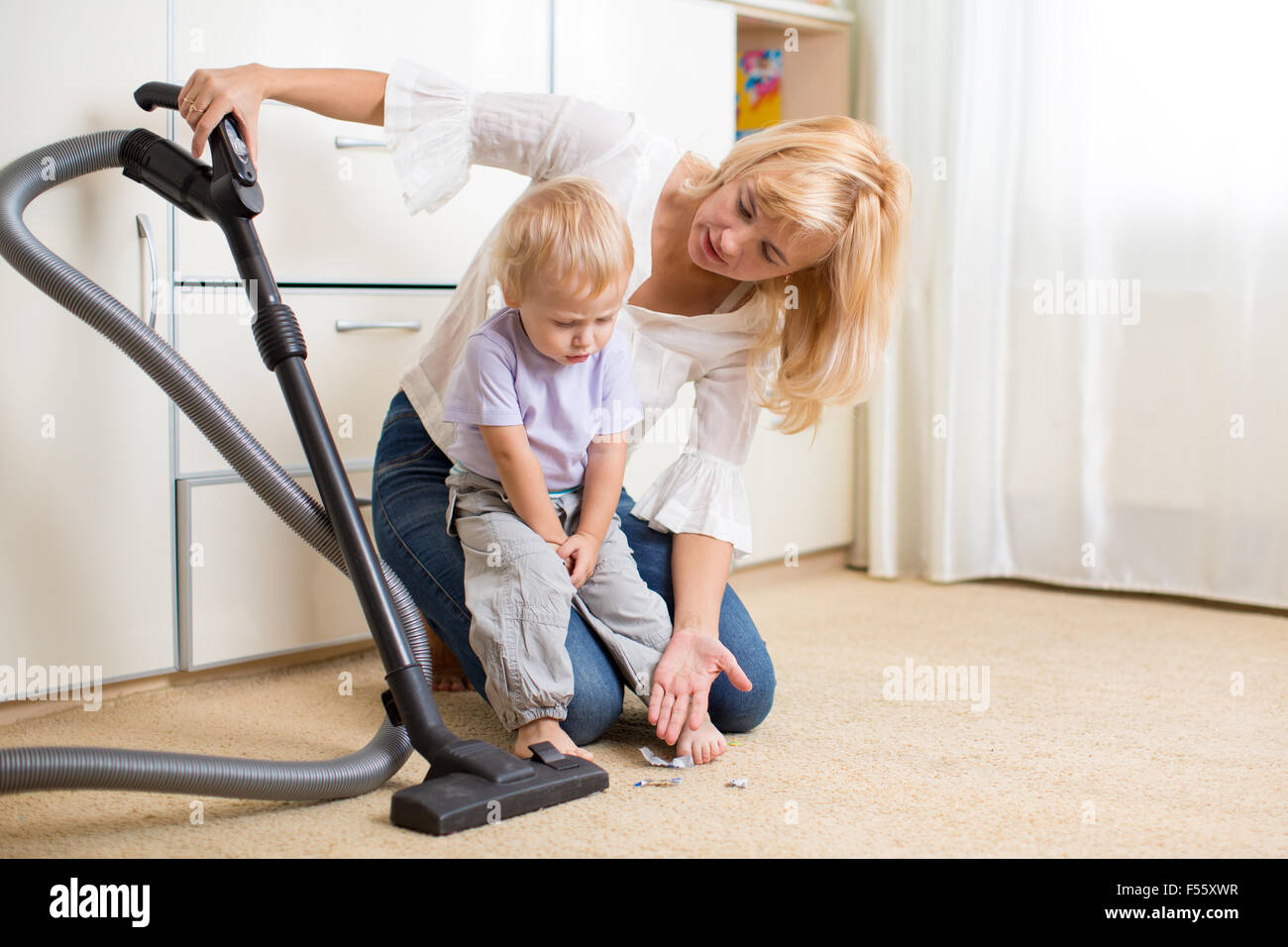 Mother teaches her child son room cleaning - Stock Image