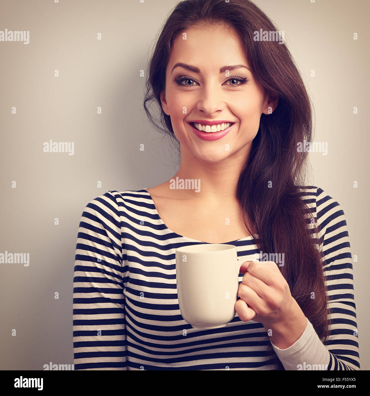 Happy toothy smiling casual young woman with cup of tea. Vintage closeup portrait - Stock Image