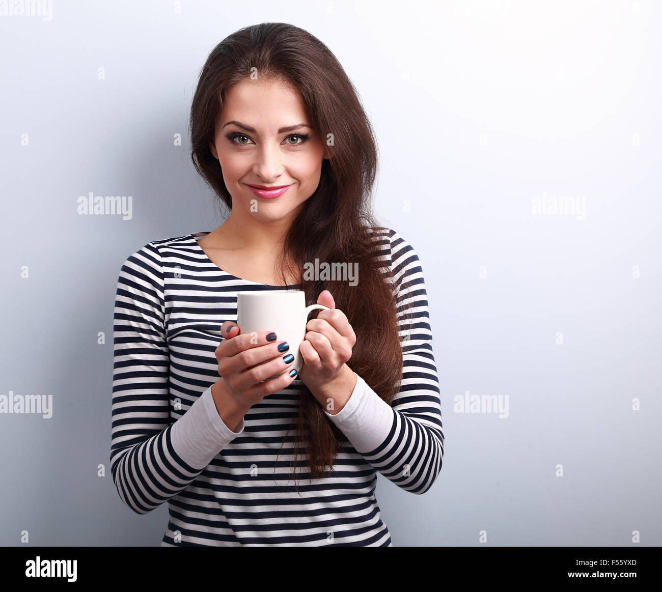 Cute young casual woman holding in hand cup of tea and smiling on blue background - Stock Image