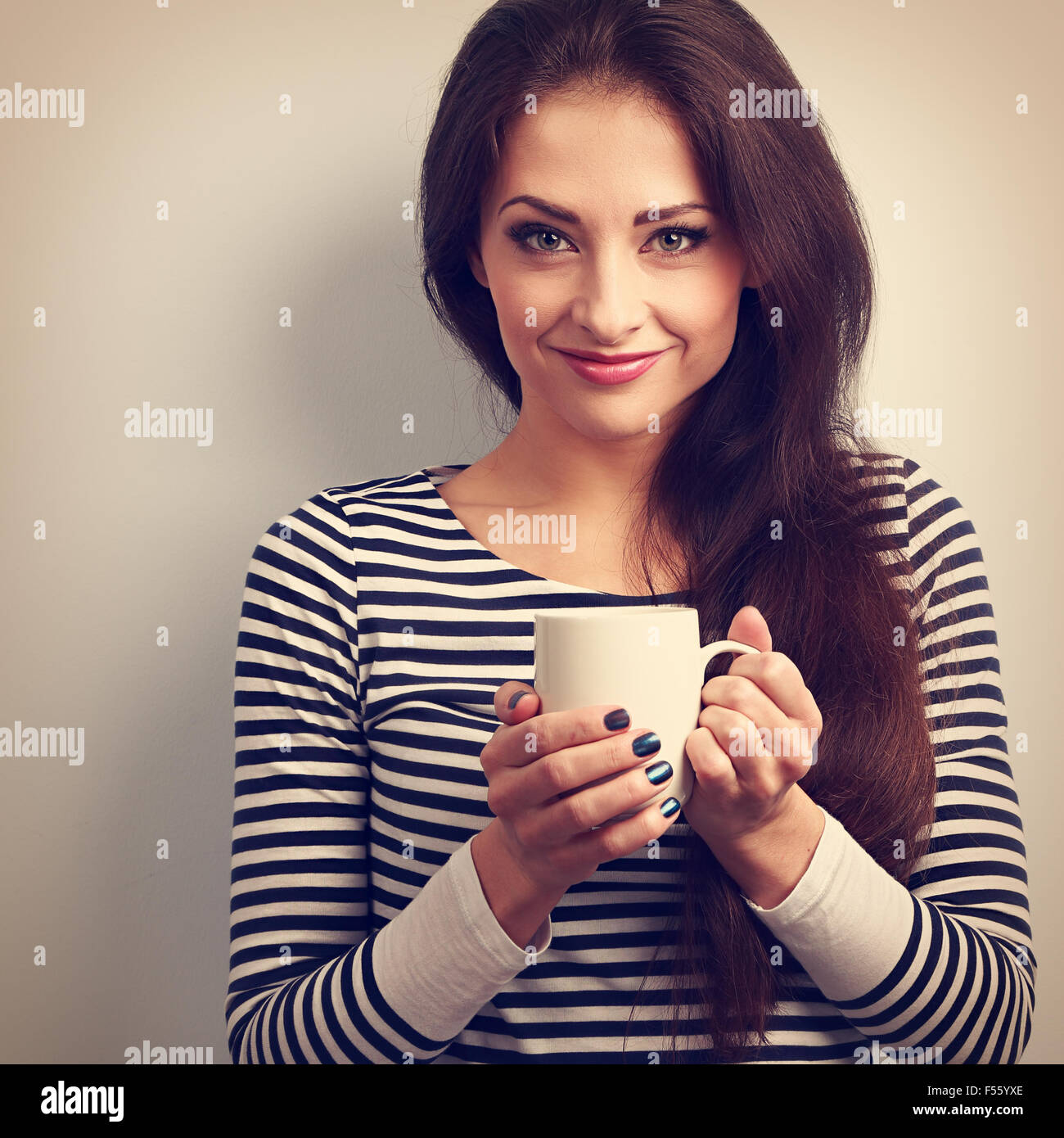 Cute young casual woman holding in hand cup of tea. Vintage toned portrait. Closeup - Stock Image