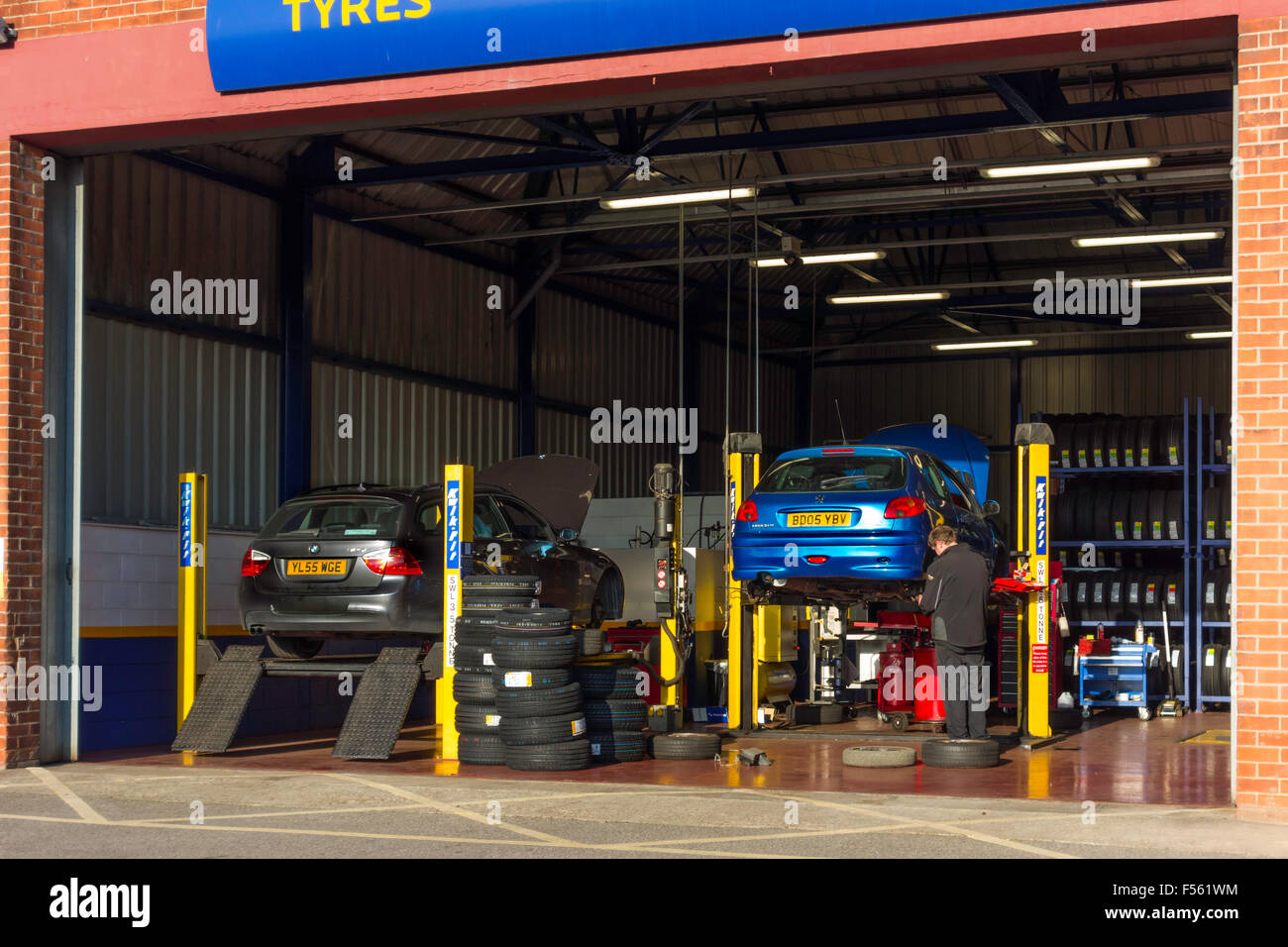 Technician working at a Kwik Fit motor vehicle tyre and exhaust repair and replacement facility - Stock Image