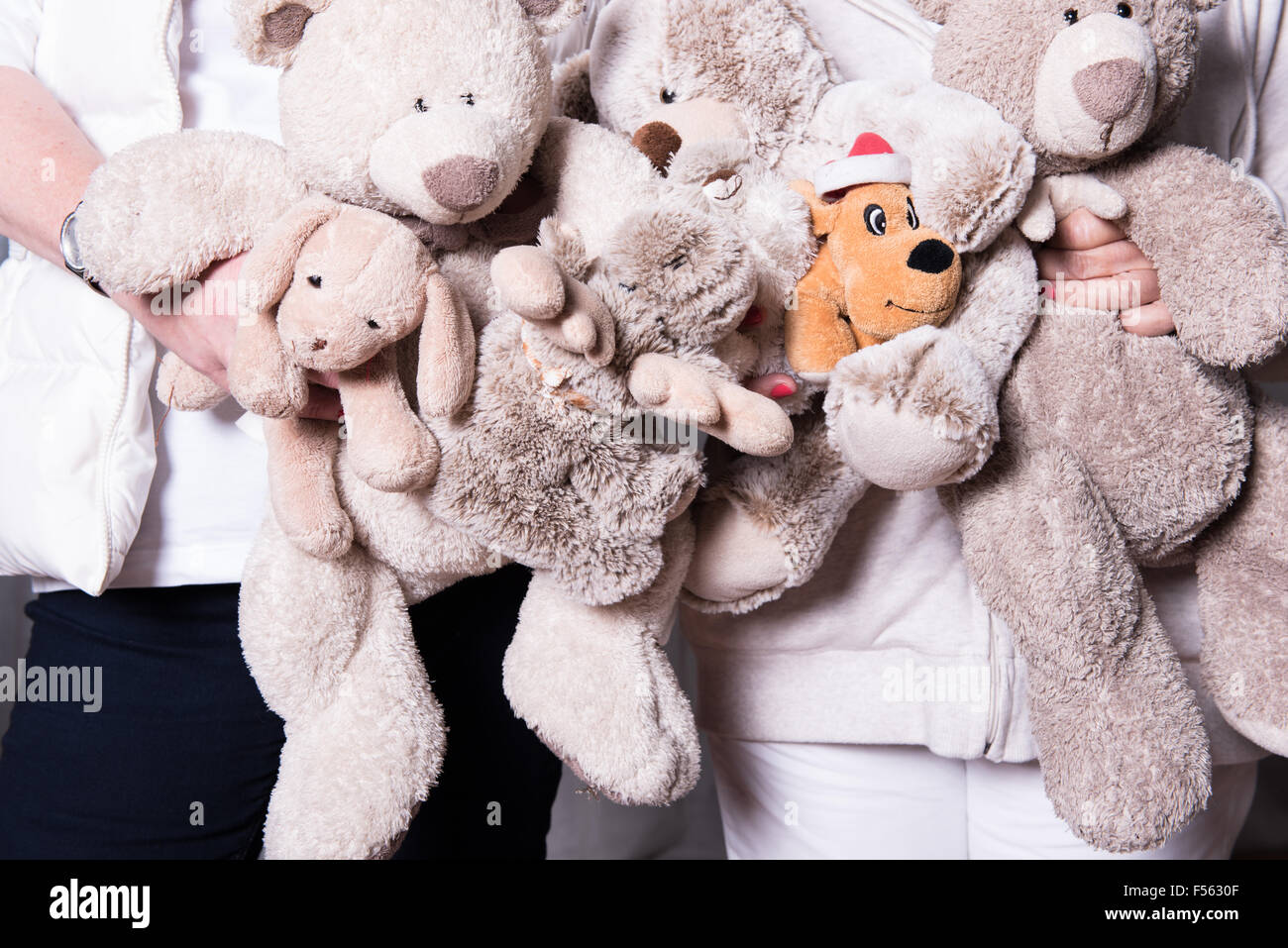 female helpers offer toys to refugee children - Stock Image