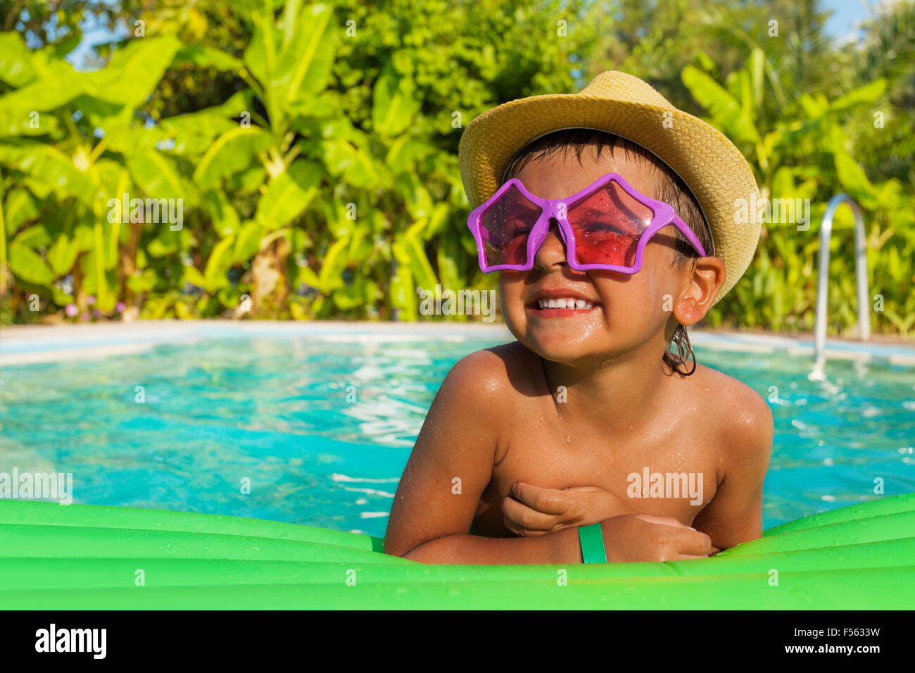 Happy boy in shaped sunglasses on green airbed - Stock Image