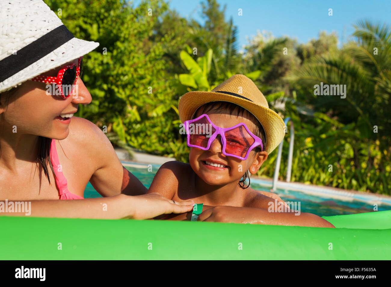 Happy mother and boy wearing sunglasses in pool - Stock Image