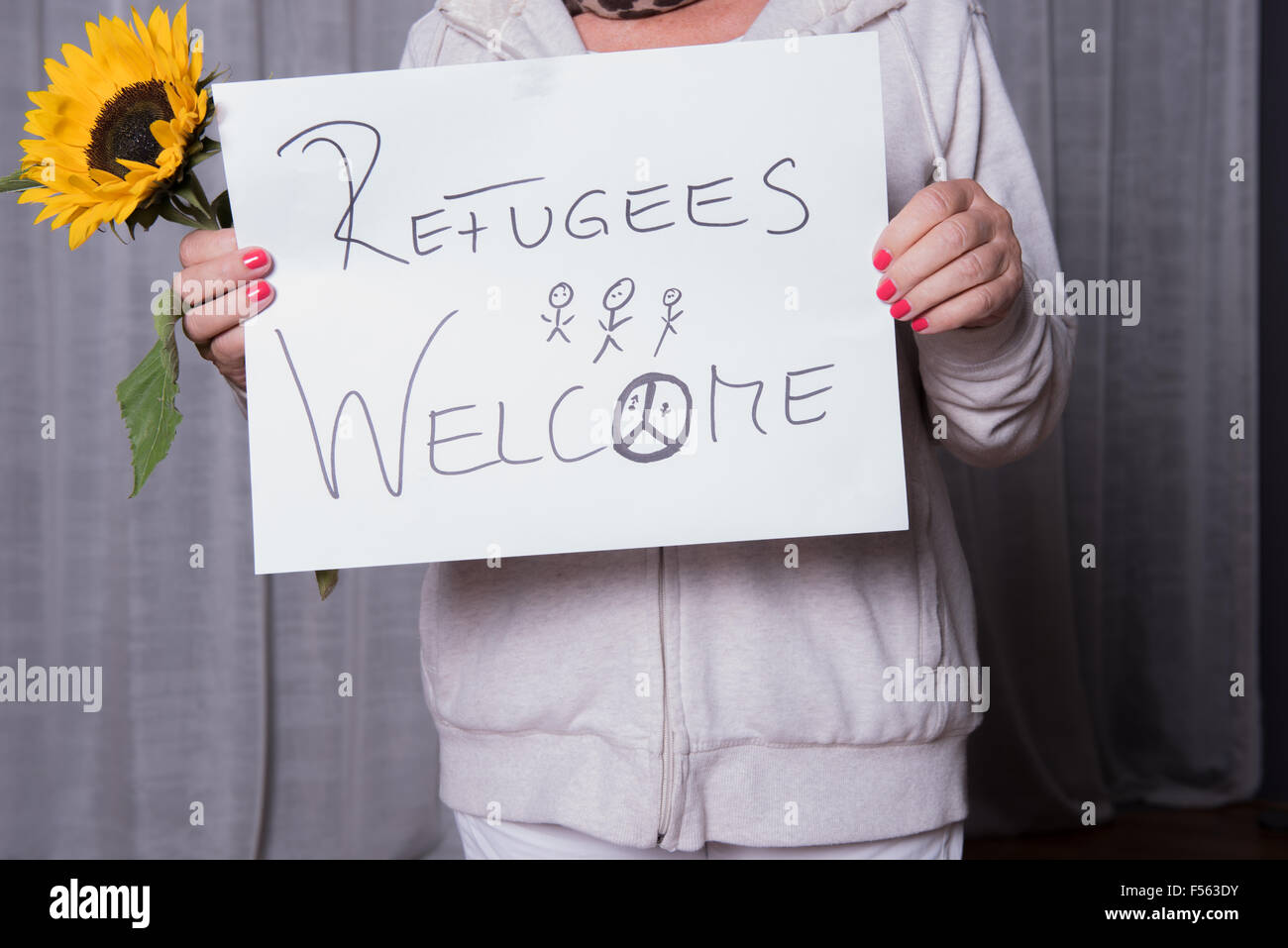 female helper welcomes refugees - Stock Image