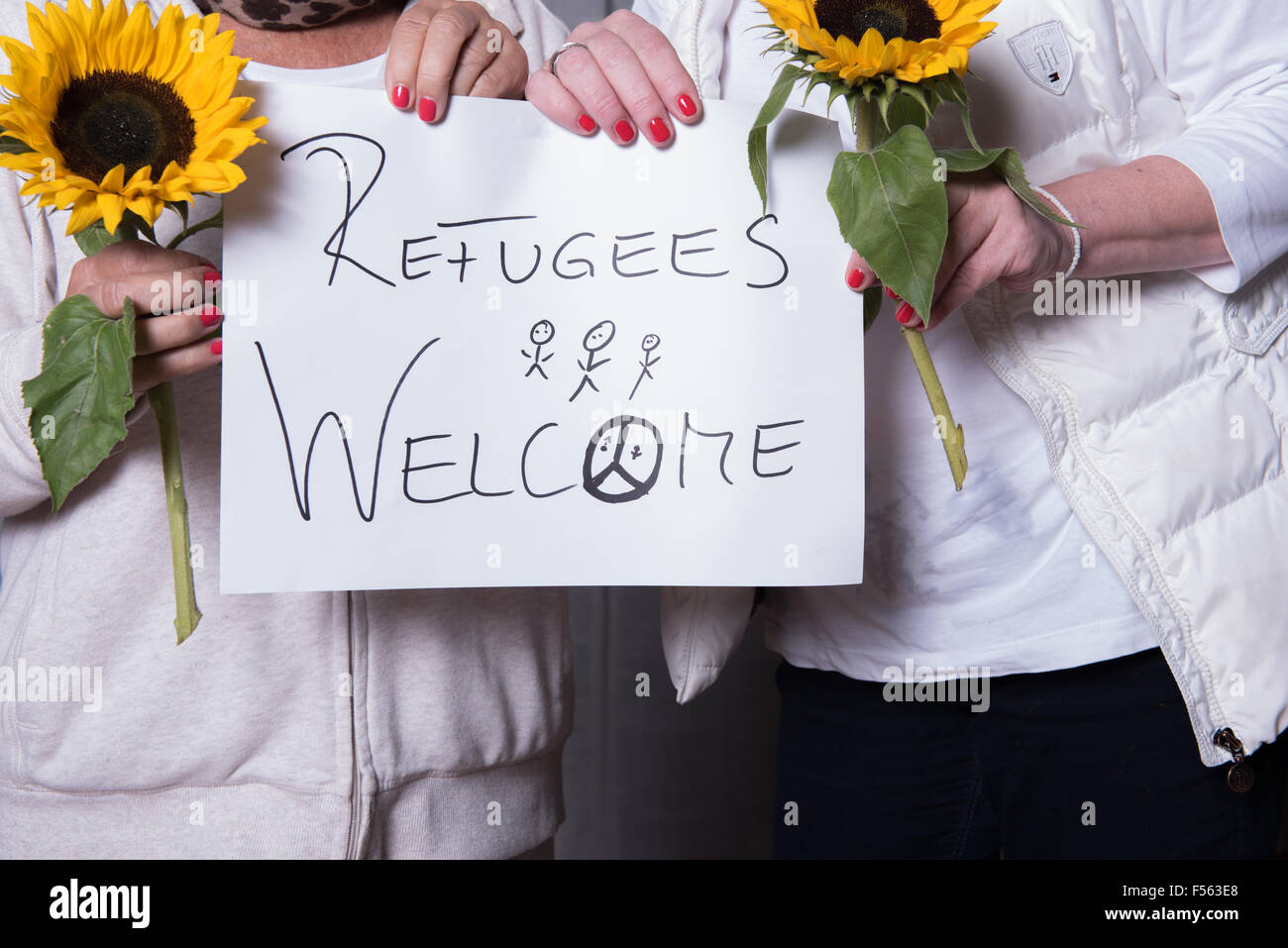 female helpers welcome refugees - Stock Image
