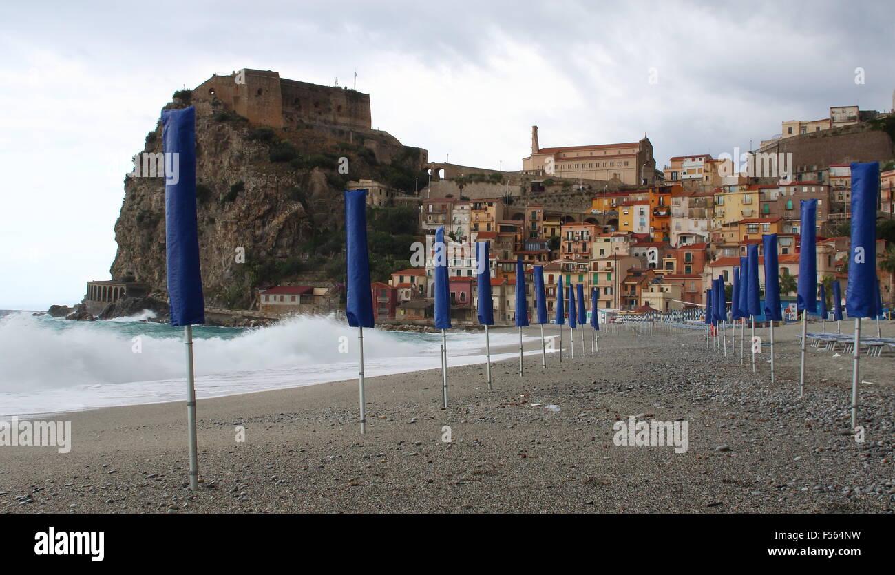 Beach scene with blue umbrellas at Scilla, Italy - Stock Image