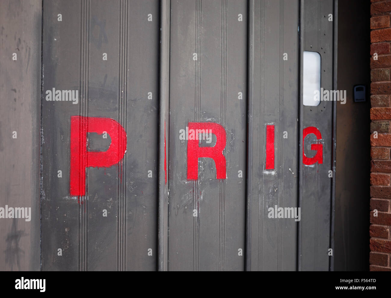 'PARKING' on a folding metal door seen from the side so as to read 'PRIG'. - Stock Image