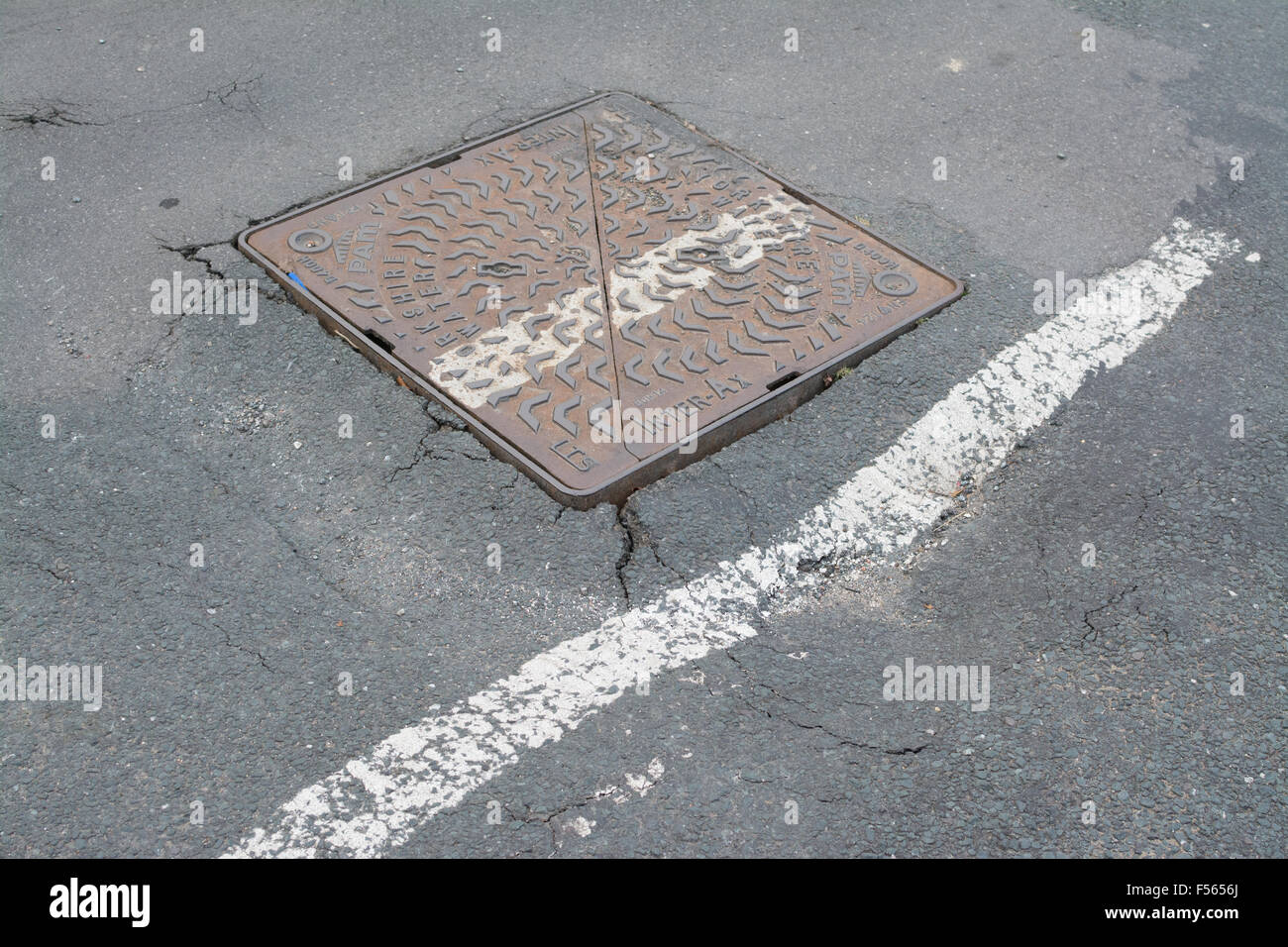 Public road cracking and sinking around drain access cover giving a  large pot hole - Sheffield, South Yorkshire, - Stock Image