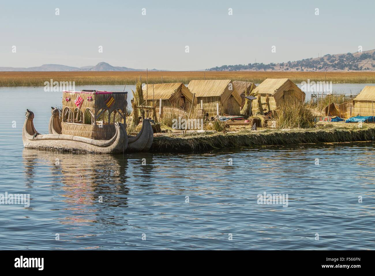 View of floating island Uros, Lake Titicaca, Peru, Bolivia and reed boat with its reflection. - Stock Image