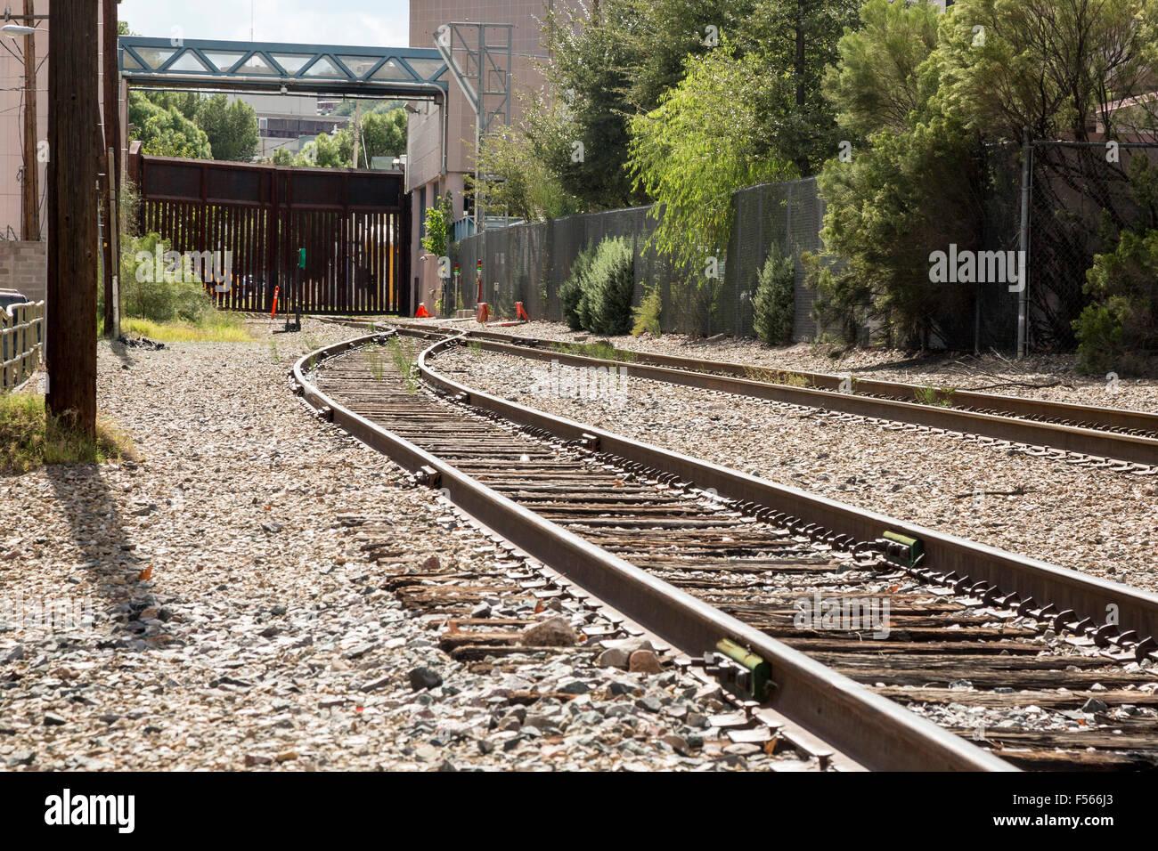 Nogales, Arizona - A fence blocks train tracks at the international border corssing into Mexico. - Stock Image