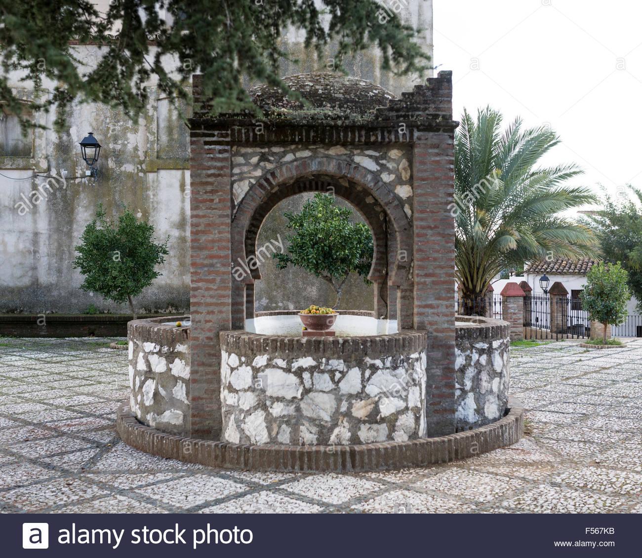Water Well in San Juan Bautista Church courtyard in Linares, Sierra de Huelva, Andalusia Spain - Stock Image