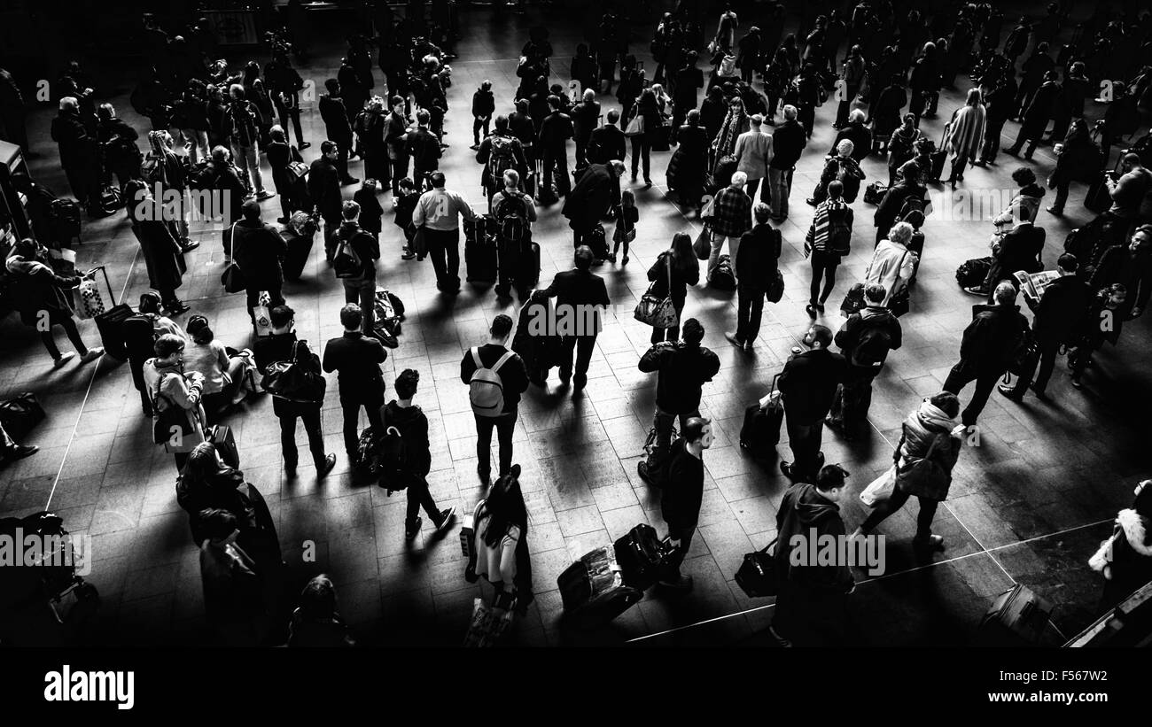 A crowd of people waiting in front of the timetable in London Kings Cross station for a train, London, UK - Stock Image