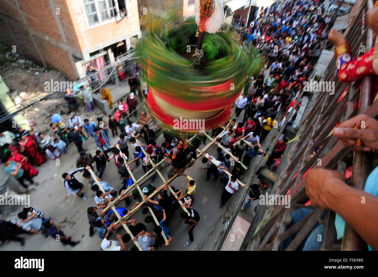 Kathmandu, Nepal. 28th Oct, 2015. Locals carry as well as rotates top part of a chariot of Lord Narayan across the - Stock Image