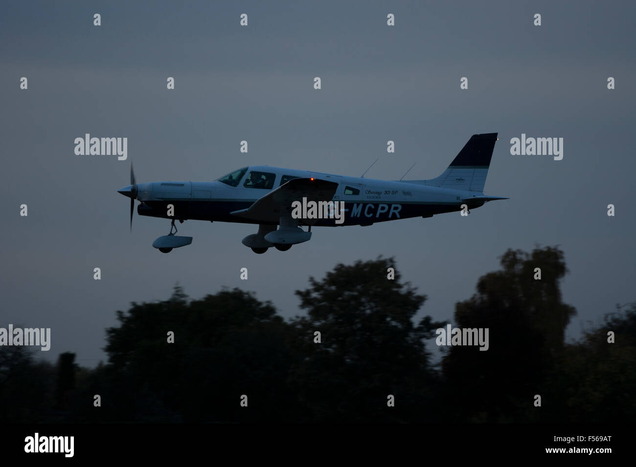 Piper PA32 Turbo Saratoga at Wellesbourne Airfield landing in almost darkness, UK (G-MCPR) - Stock Image