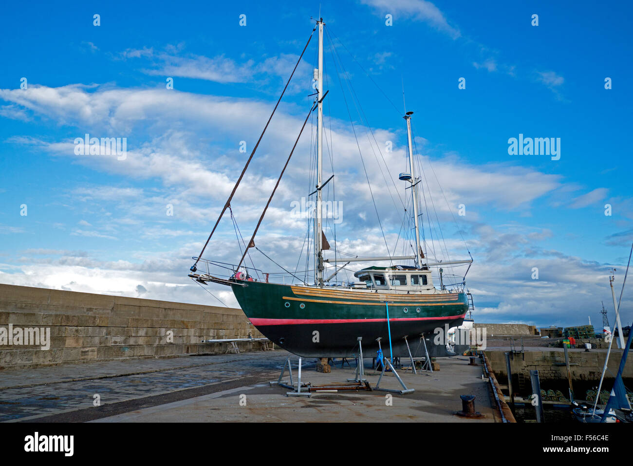 A yacht out of water for repairs on the quay at Lossiemouth Harbour, Moray, Scotland, UK. - Stock Image