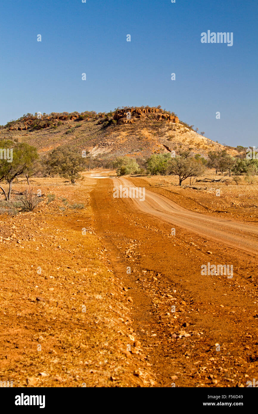 Outback road across red arid stony landscape with trees & flat topped hill / mesa on distant horizon under blue - Stock Image