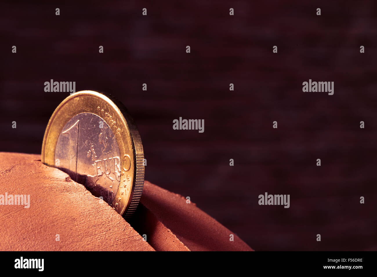 closeup of a coin of one euro in the hole of an earthenware piggy bank - Stock Image