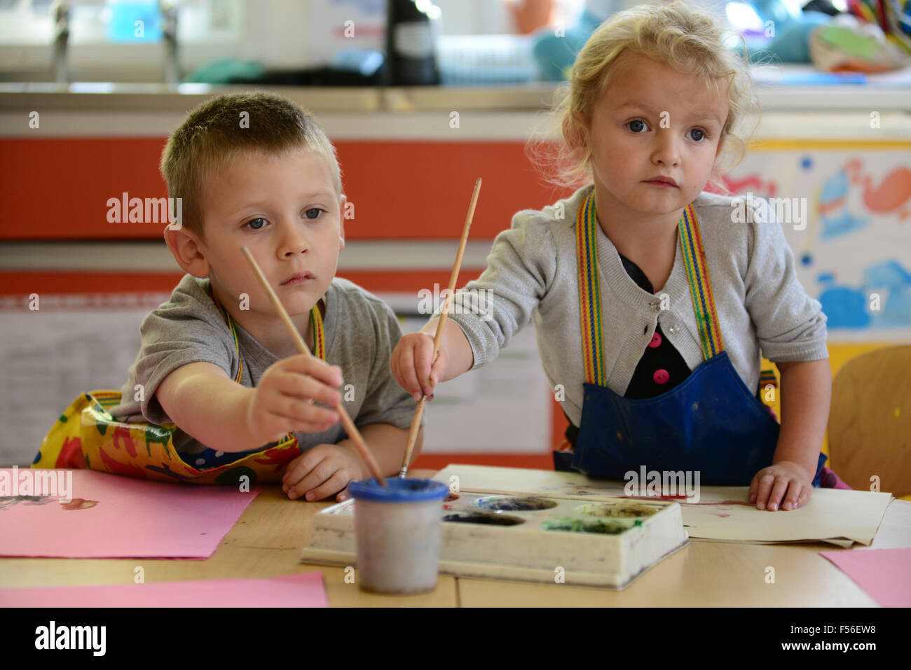 A little girl & boy painting at nursery school. Stock Photo