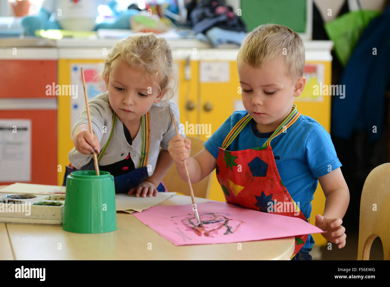 A little girl & boy painting at nursery school. - Stock Image