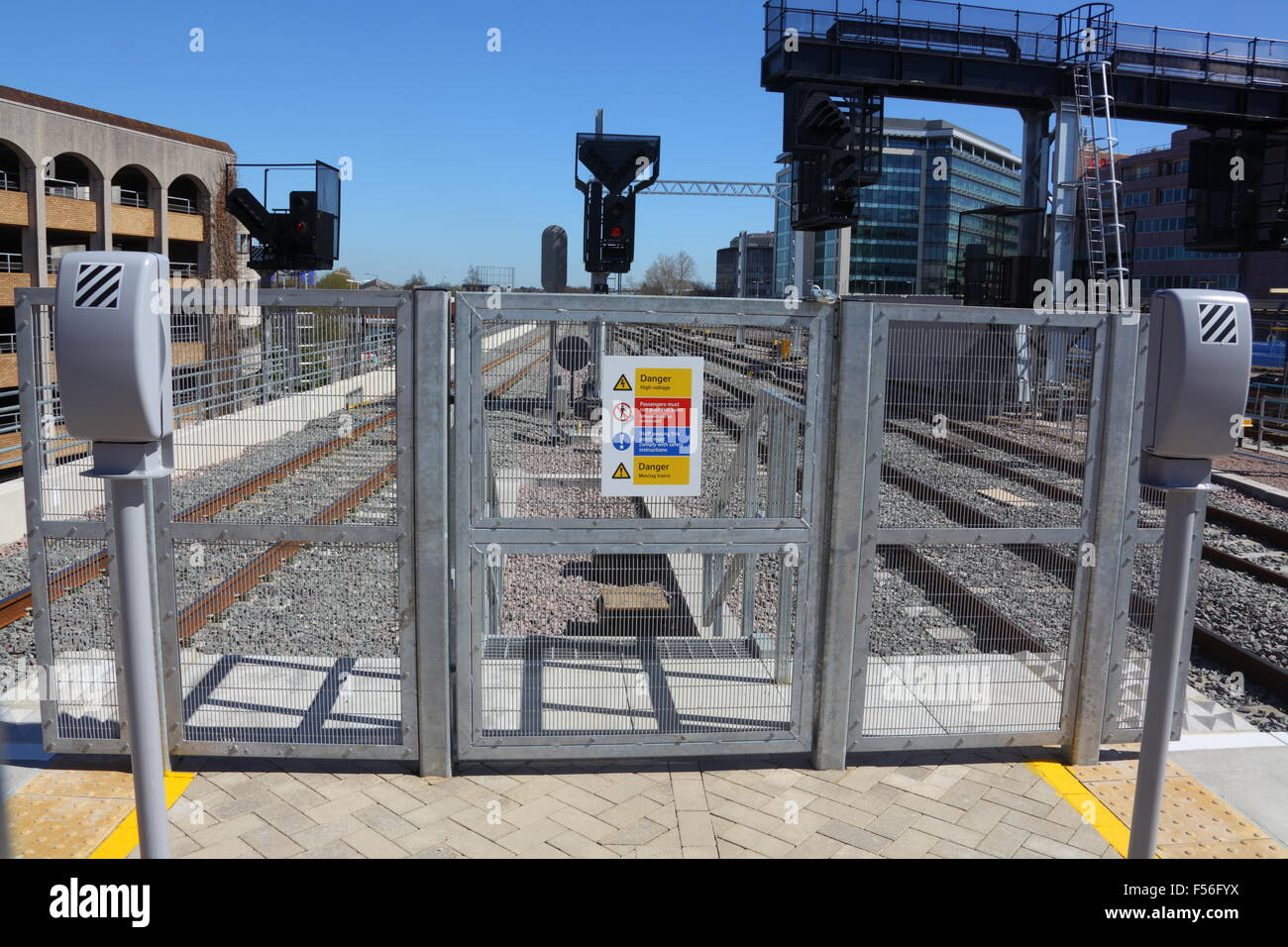 A new security fence on the end of a train station platform with a safety notice attached, also shown are two telephone - Stock Image