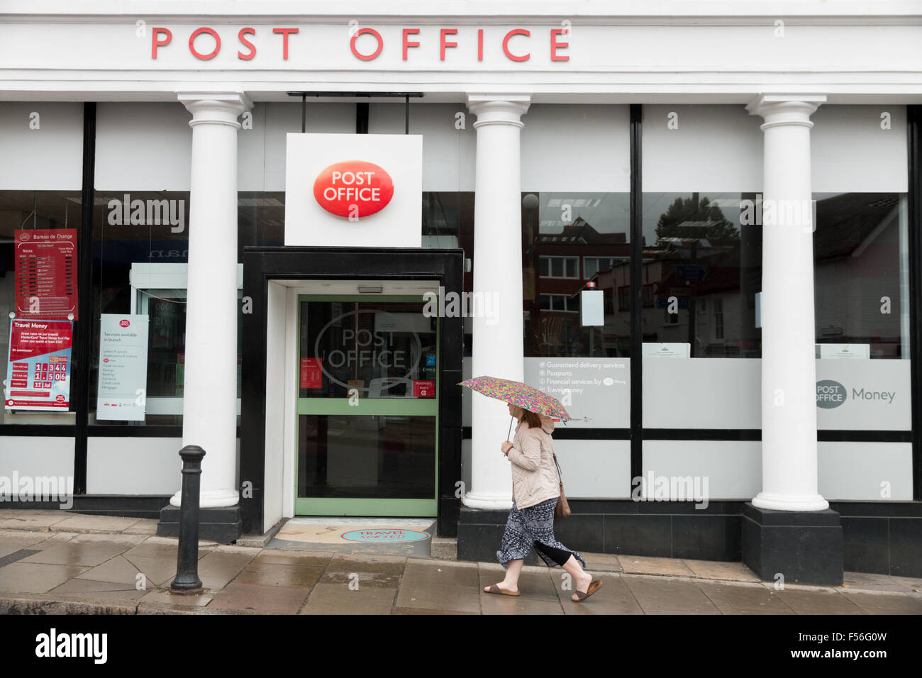 A woman enters Guildford Town Post Office building in the rain Stock Photo