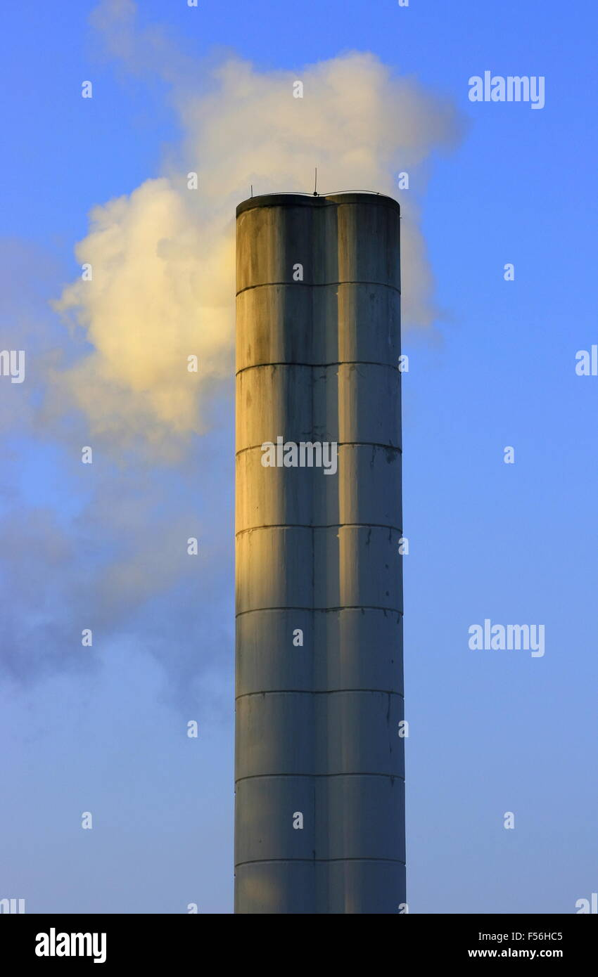 Large chimney sent clouds of steam into the blue sky - Stock Image