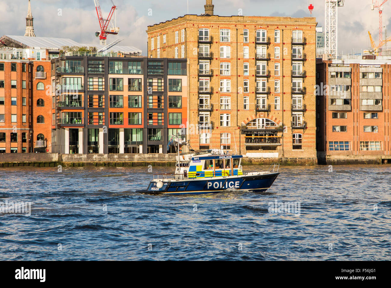 Marine Police Force or Thames River Police boat on the River Thames passing the Samuel Pepys pub in the riverbank, - Stock Image