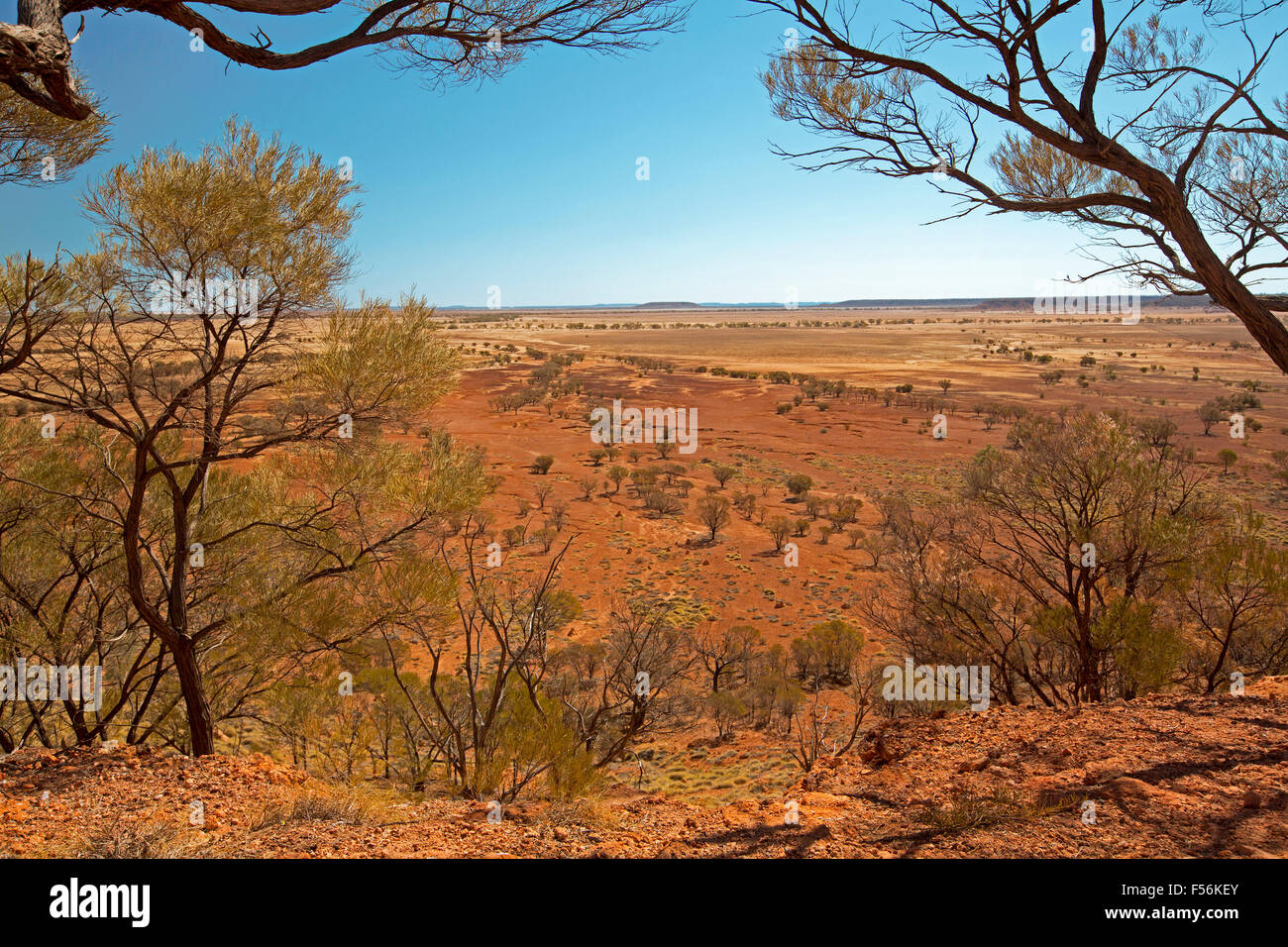 View from hilltop lookout of barren red outback plains stretching to horizon under blue sky during drought at Bladensburg - Stock Image
