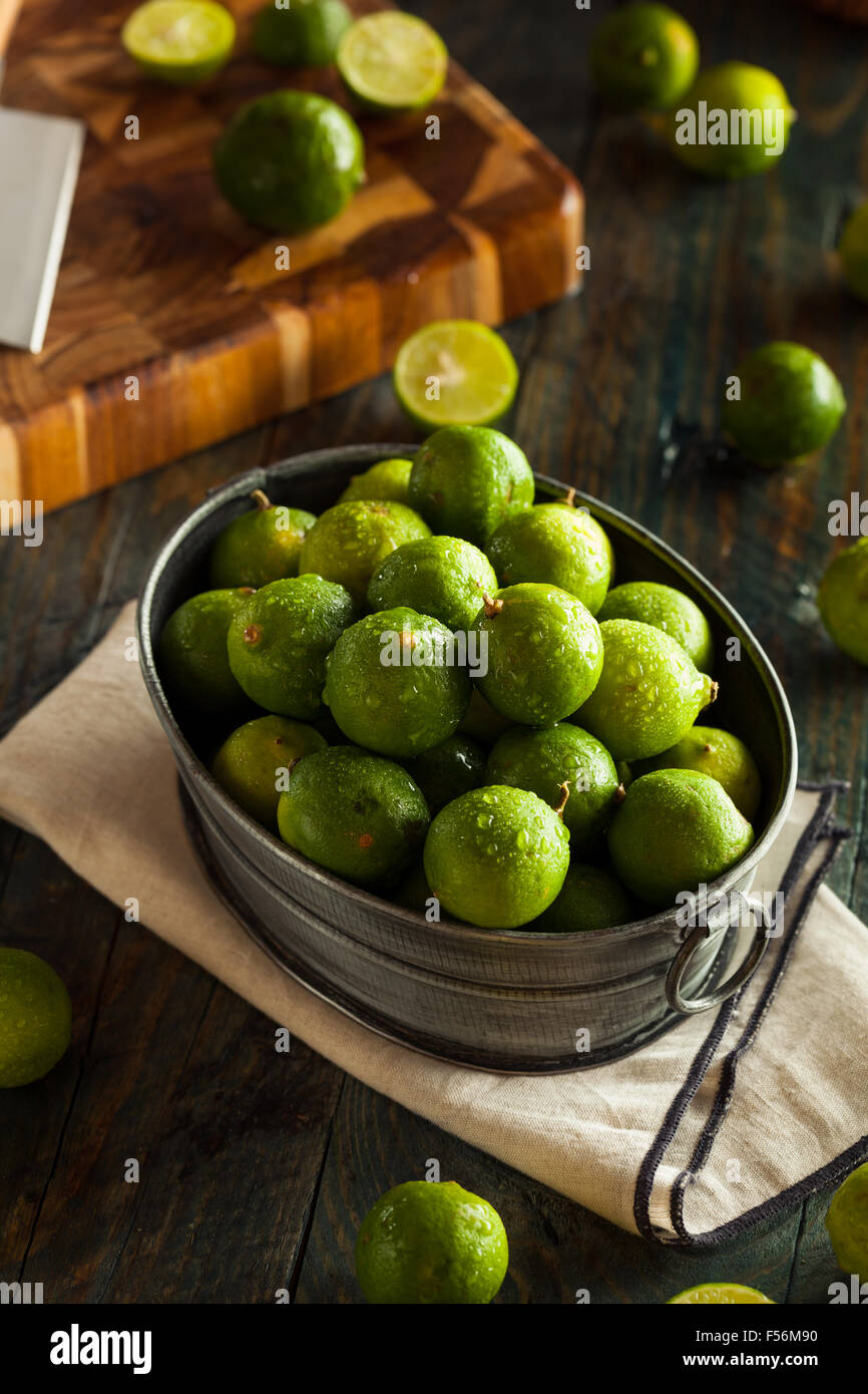 Raw Green Organic Key Limes in a Bowl - Stock Image