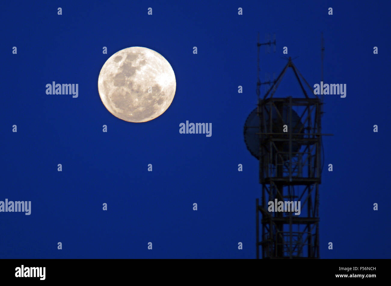 Full moon rise against silhouettes of television and radio antenna on evening dusk sky background. Outer space concept - Stock Image