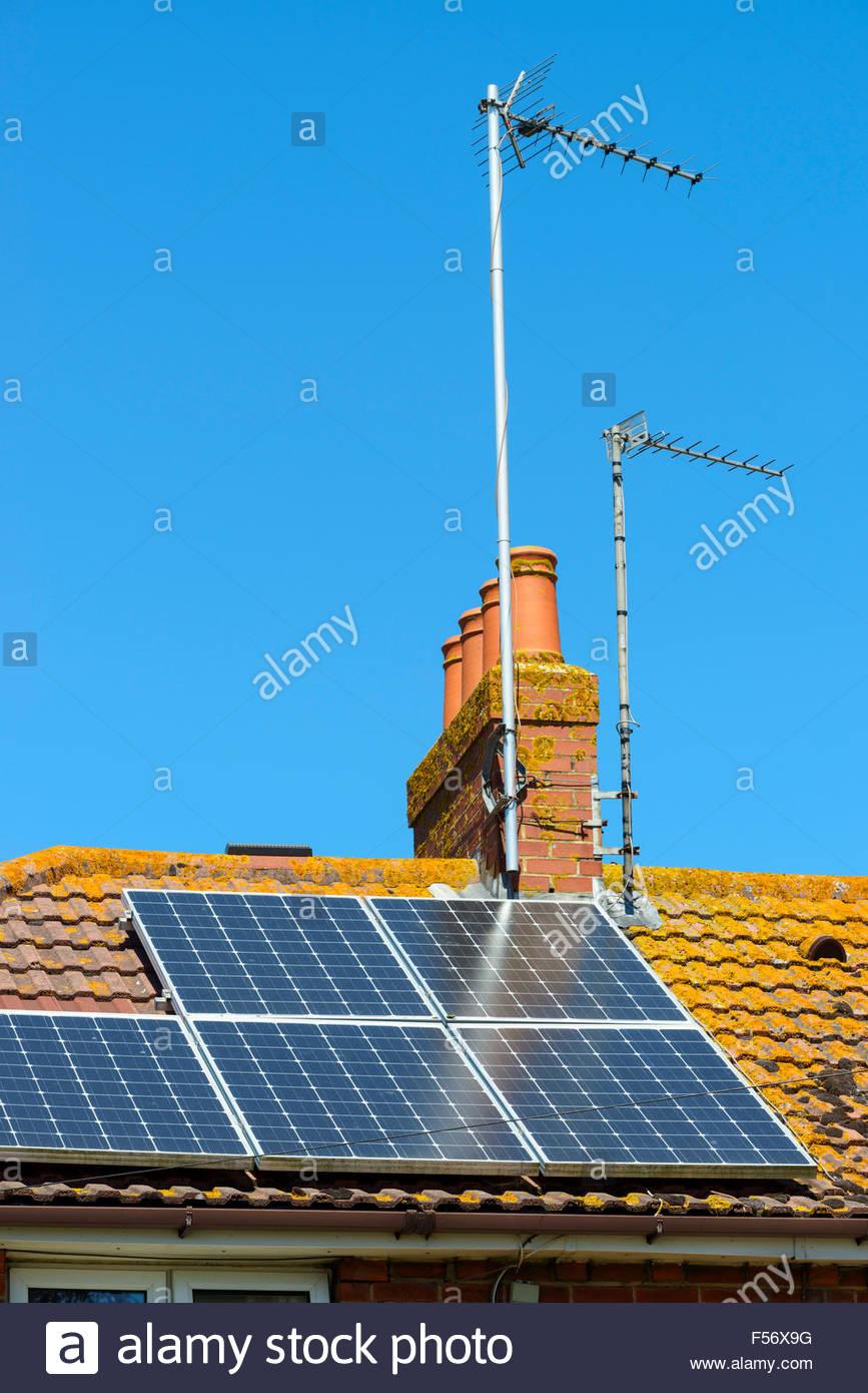 Domestic solar panels on house roof, Poole, Dorset, England, UK - Stock Image