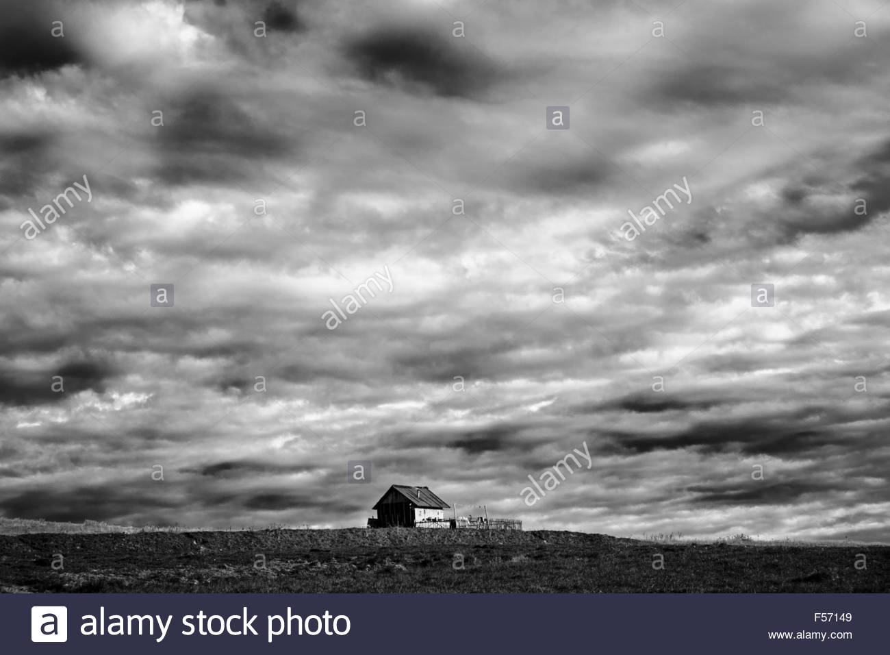 Sheepfold cottage at autumn in Transylvania, Romania.  Lowering, big dark skies. Black and white, dramatic. Stock Photo