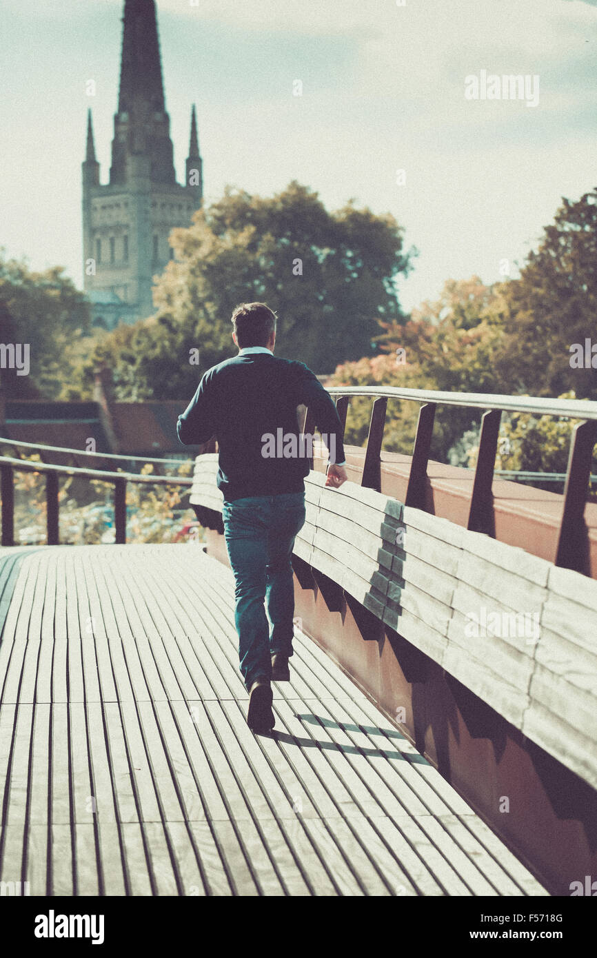Man running across urban bridge with church in the background - Stock Image