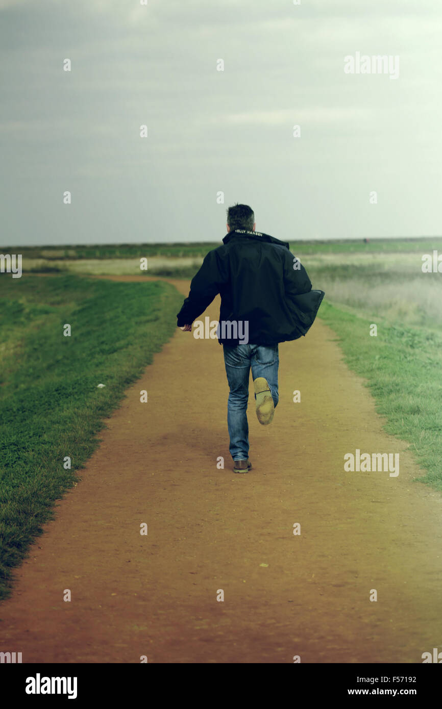 Middle aged man running in rural coastal area Stock Photo