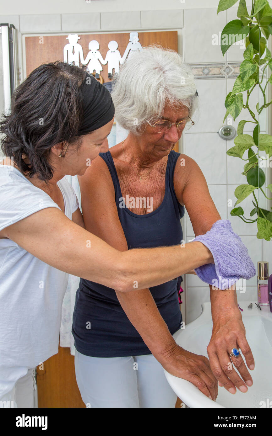Elderly care at home, Nurse cares for an elderly woman, washing, toiletries in the bathroom, Stock Photo